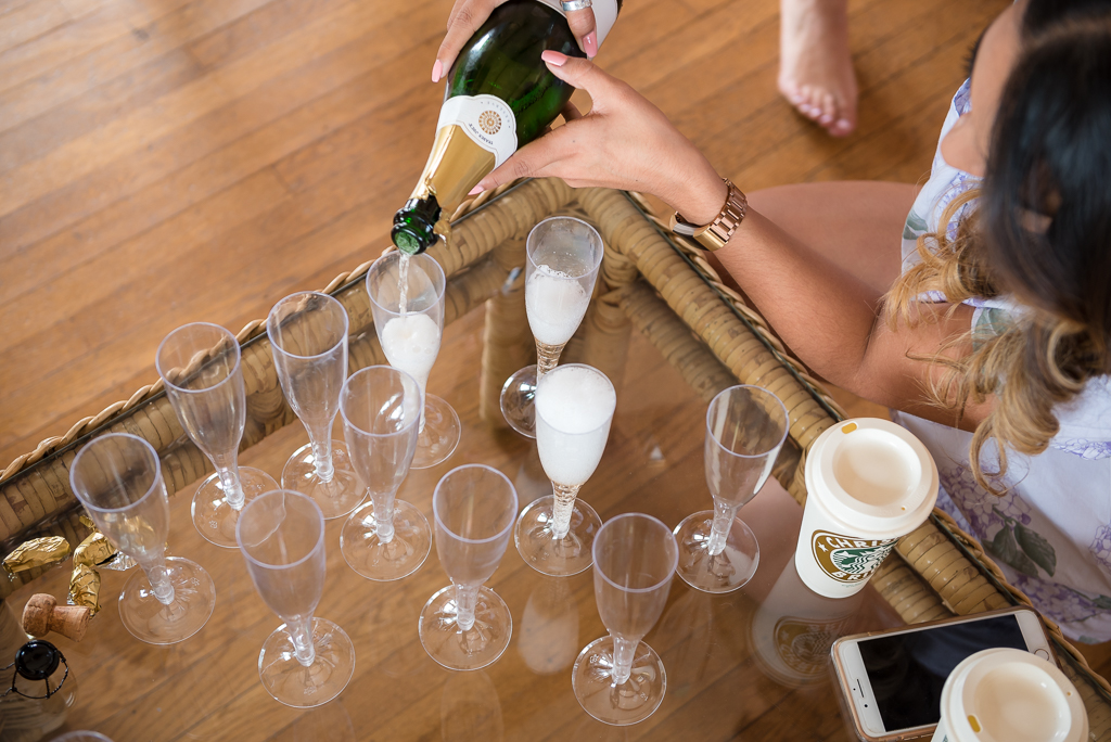 Photo of a bride pouring champagne into flutes.