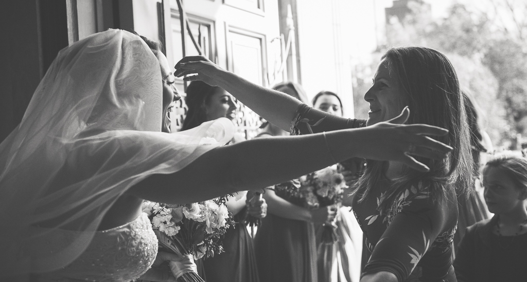 Black and white photo of a bride reaching out to embrace a driend.