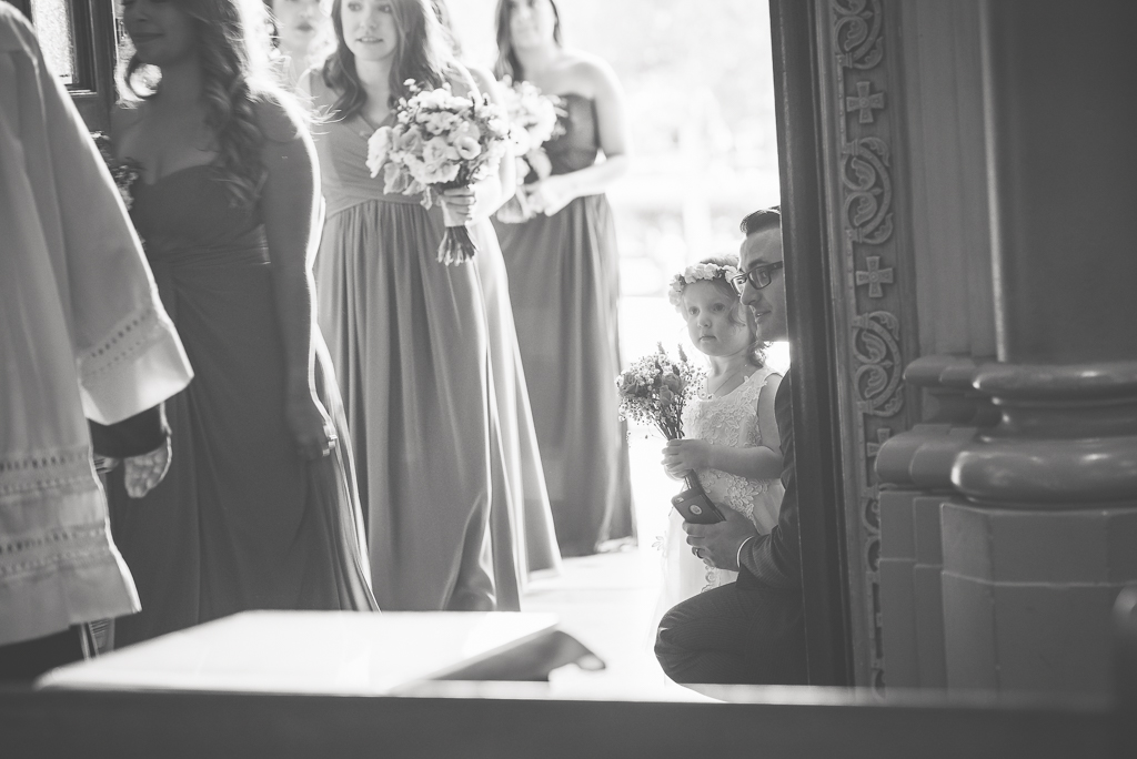 Photo of a little flowergirl looking on as the bridal party starts a processional into a cathedral.