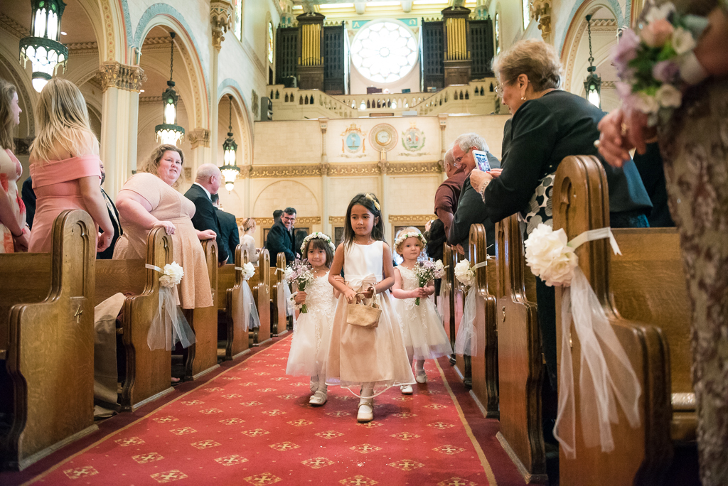 A trio of little flower girls walk down the aisle of Saints Peter and Paul Church in San Francisco.