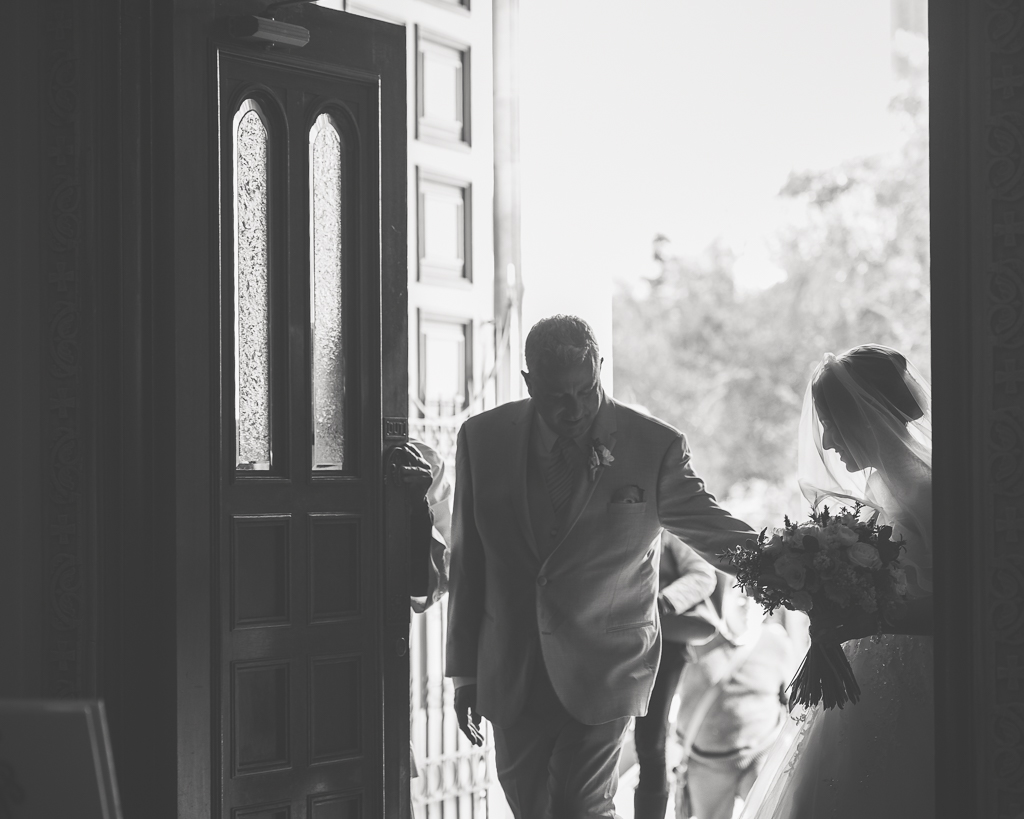 Black and white photo of a bride entering a church building with her father for her wedding ceremony.