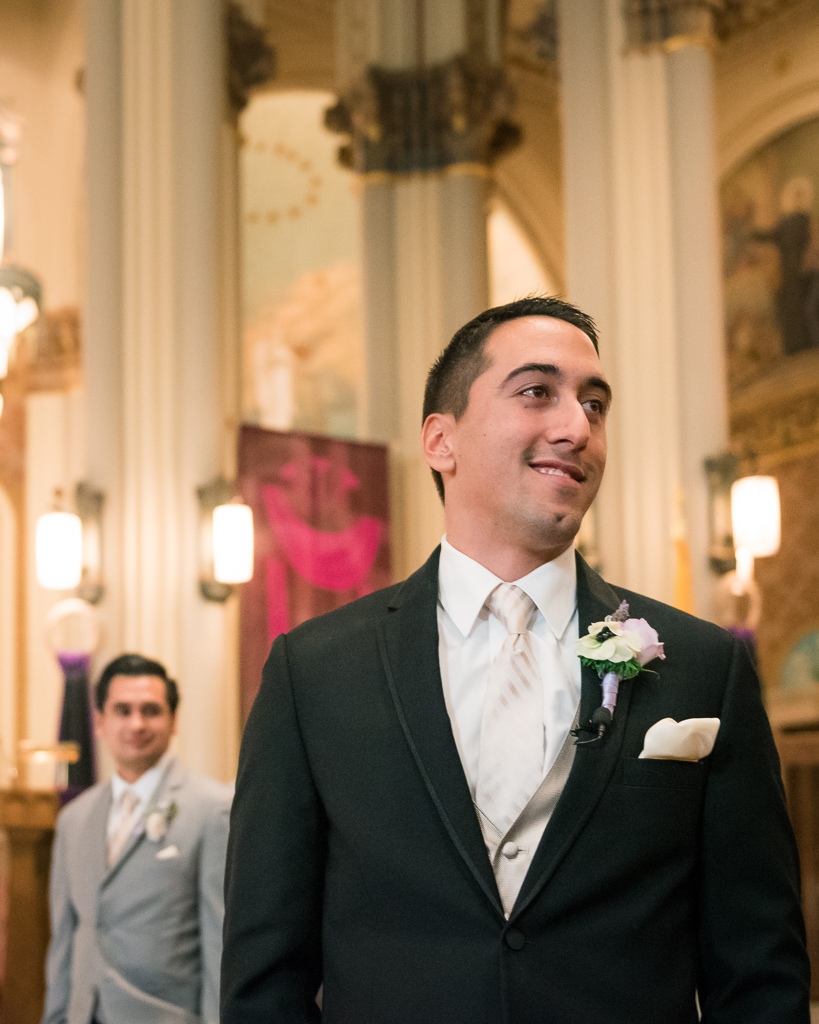 Photo of a groom looking on in anticipation of seeing his bride.
