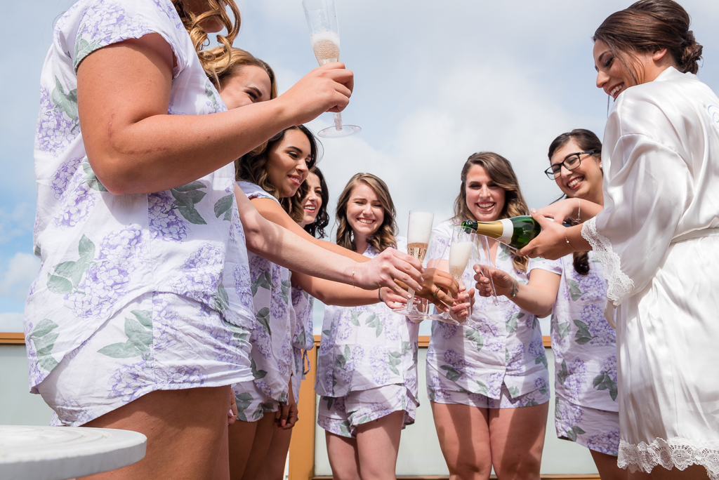 Photo of bridesmaids and the bride enjoying champaign.