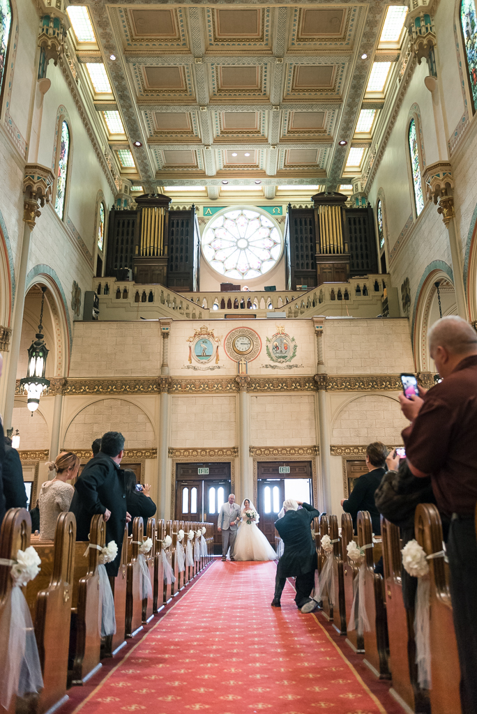 A bride and her father walk down the aisle of Saints Peter and Paul Church in San Francisco.