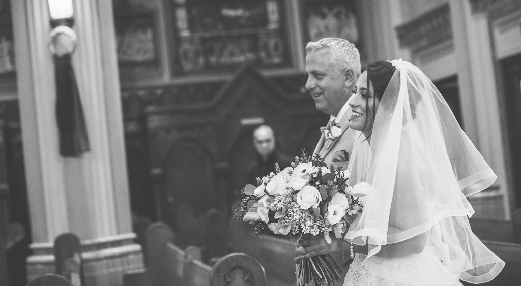 A father and daughter walk down the wedding aisle, arm in arm.