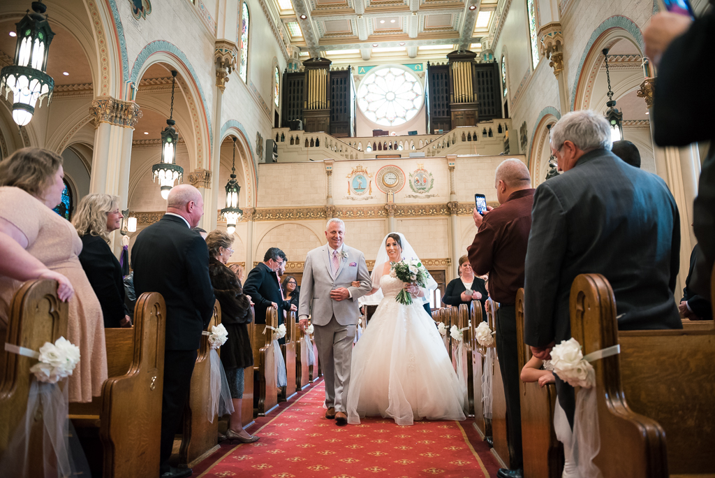 Photo of a bride and her father walking the aisle on her wedding day.