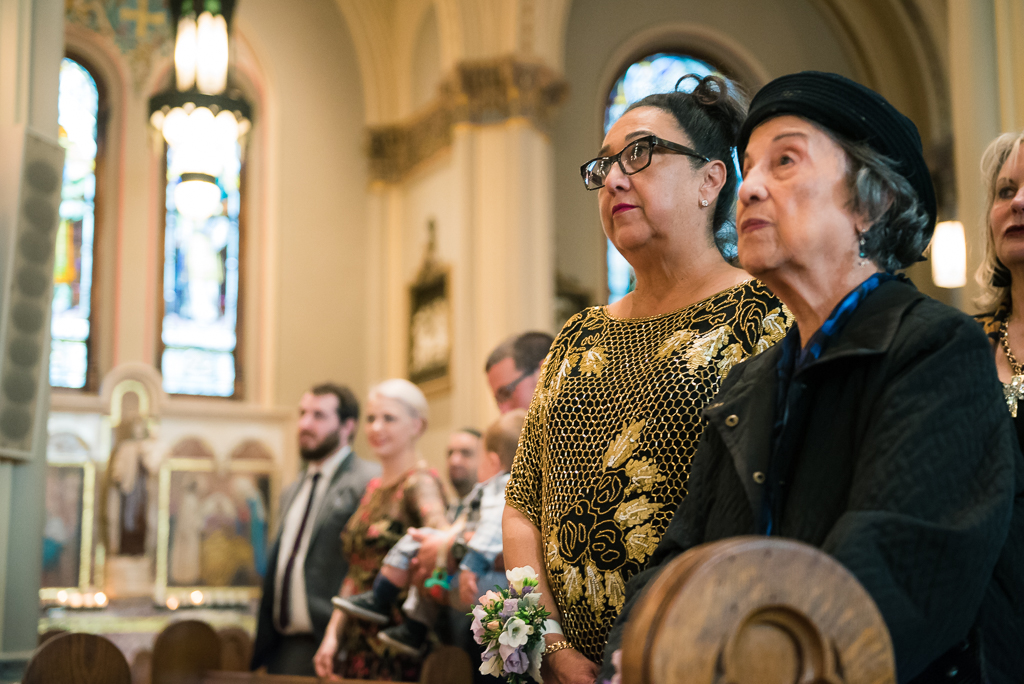 Photograph of a groom's mother and grandmother looking on at the wedding ceremony.