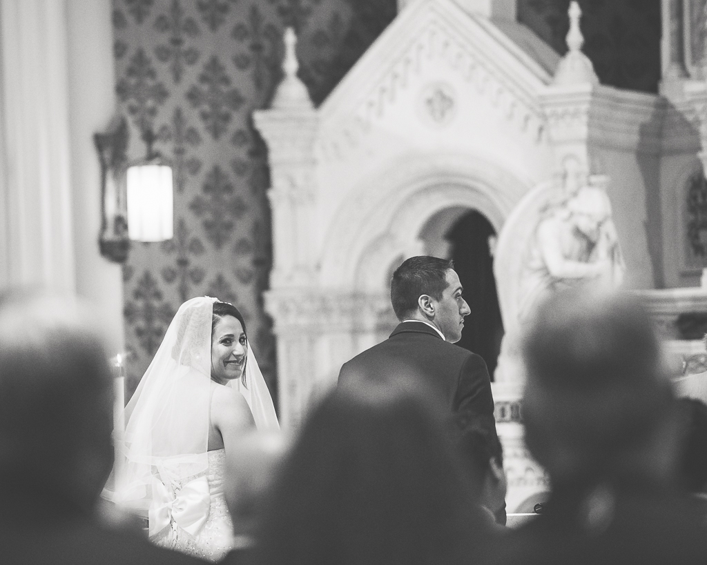 Black and white photograph of a bride and groom kneeling at the altar during a Catholic wedding.