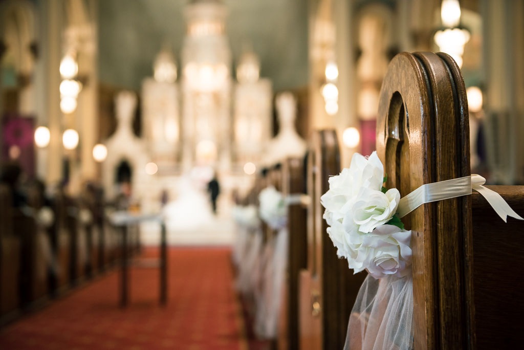 Close-up photo of a church pew during a Catholic wedding.