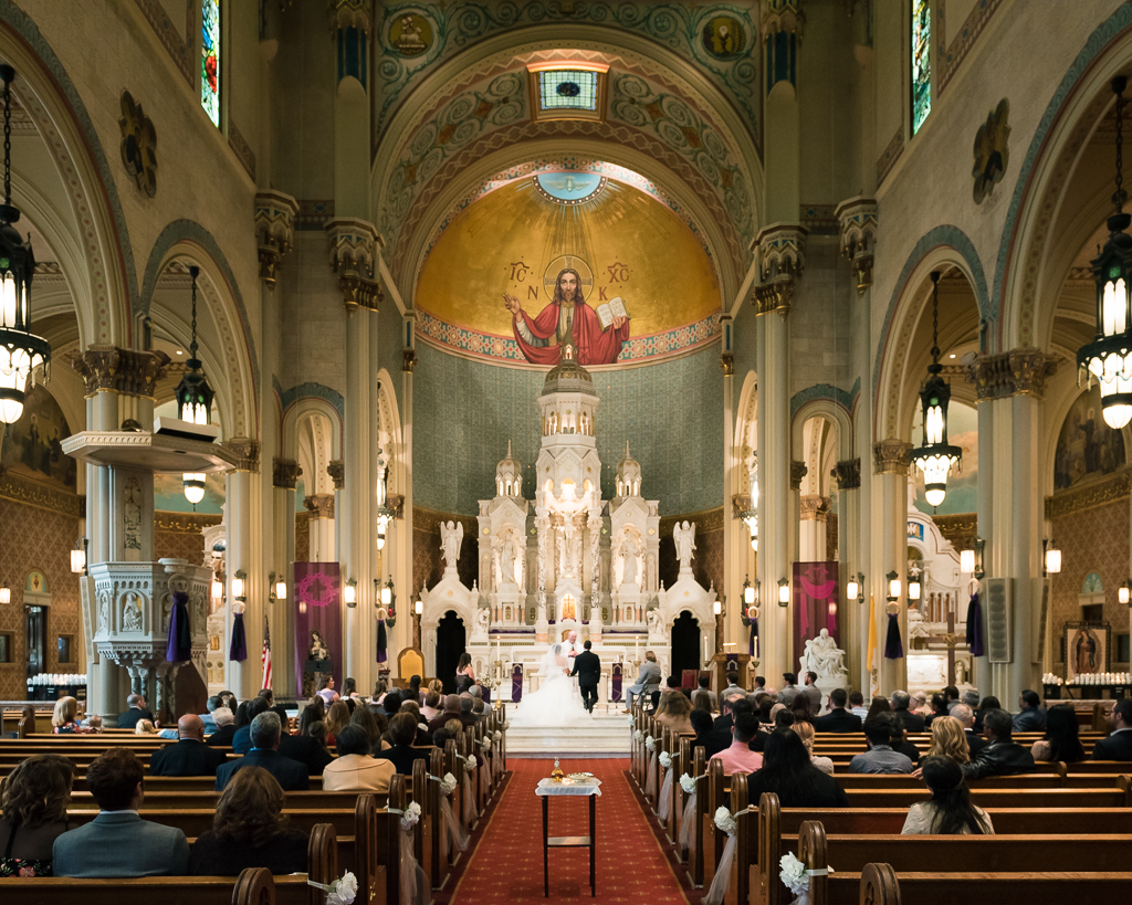 Interior photo of a catholic wedding at Saints Peter and Paul Church in San Francisco, California.