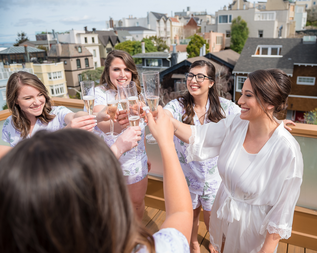 Photo of a bride and her bridesmaids making a champagne toast on a rooftop above San Francisco.