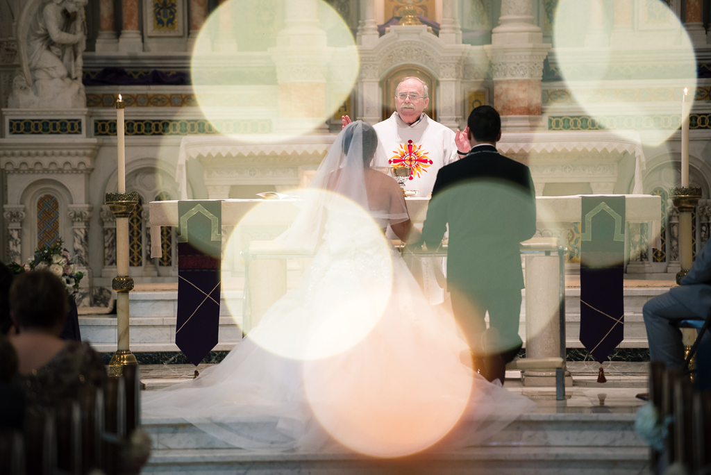 Photo of an illuminated bride and groom as they receive communion.