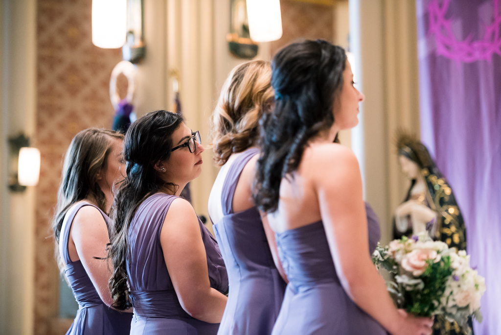 Photo of bridesmaids wearing purple looking on at a wedding ceremony.