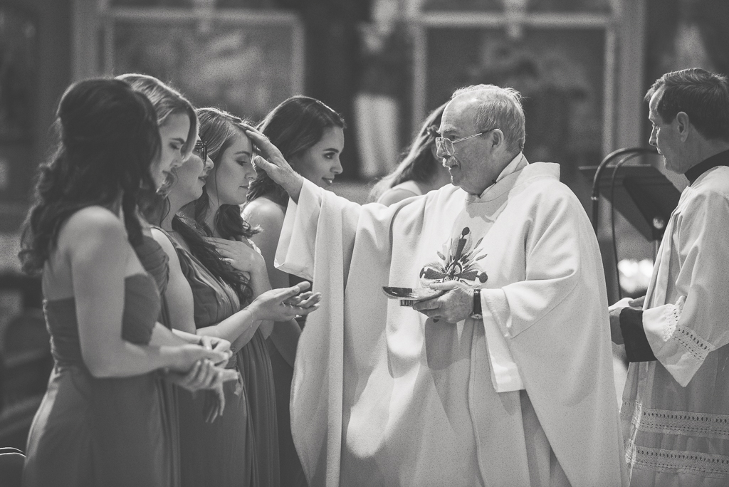 Black and white photo of a priest offering communion to bridesmaids