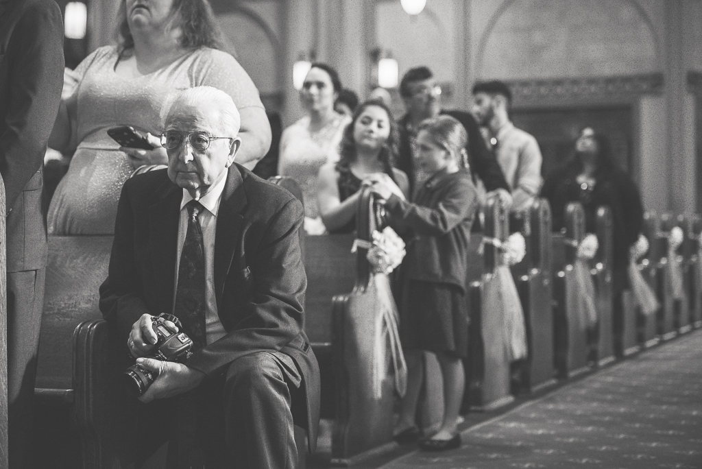 Black and white photo of a old man kneeling with a camera at a wedding.