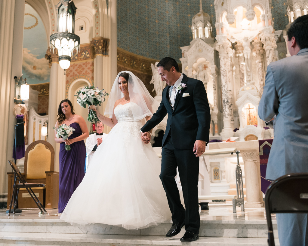An italian-american bride and groom step down from the alter after their wedding ceremony.