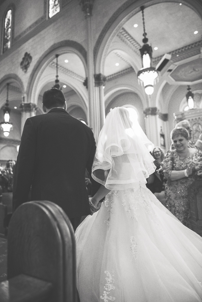 Black and white photo of a bride and groom walking back down the aisle after their wedding ceremony.