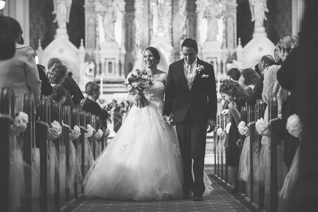 Sweet black and white photograph of italian american newlyweds walking down the aisle after their ceremony.