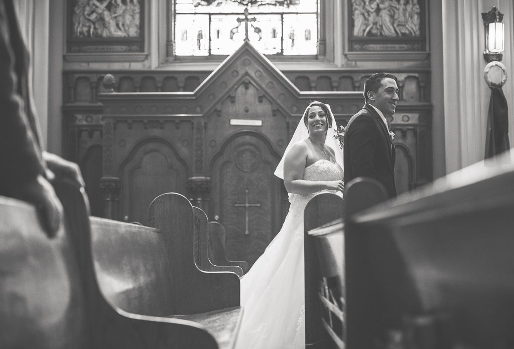 Candid black and white photo of a bride and groom walking past pews.