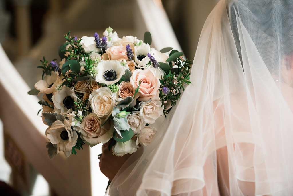 A beautiful photo of a bride holding her wedding bouquet as she walks away from the camera.