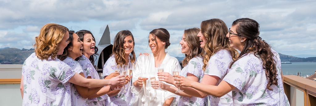 Photo of a bride and bridesmaids toasting with chapagne on a Bay Area rooftop.
