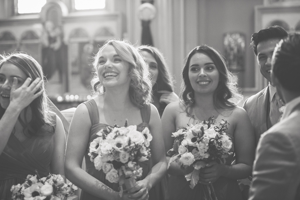 Black and white candid photo of a bridesmaid looking on at the bride after a wedding.