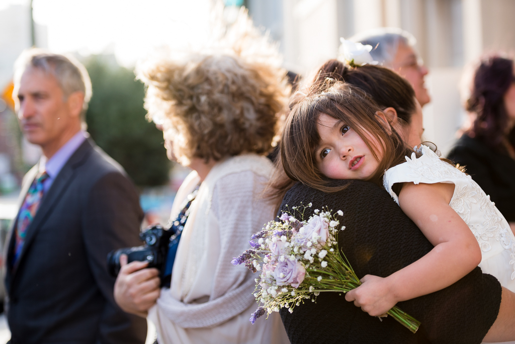Candid wedding photo of a mother carrying a tired flower girl.