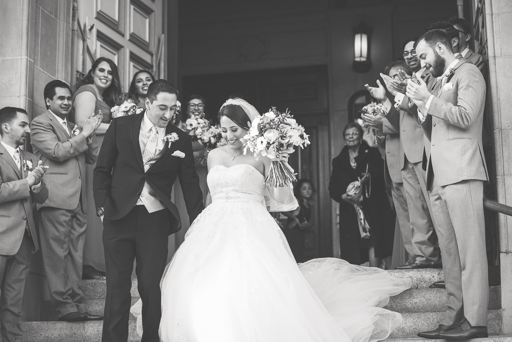 Black and white photo of a bride and groom walking out of a church after their wedding.