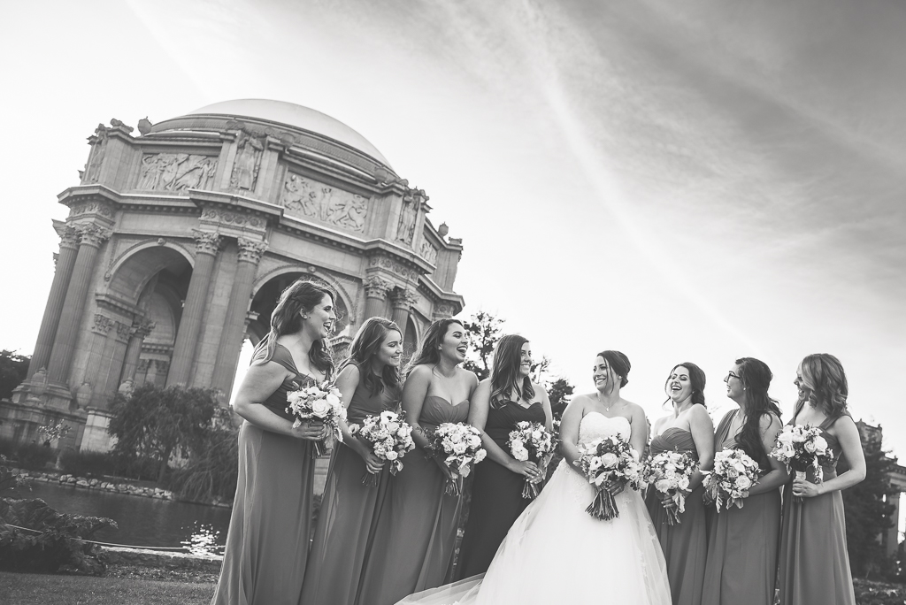 Black and white photo of bridesmaids joking near the Palace of Fine Arts.