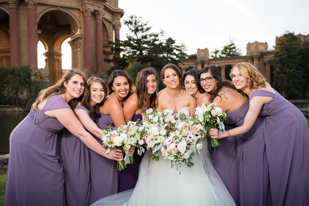 Bridemaids and a bride pose with their bouquets in a cluster with an colonnade in the background.