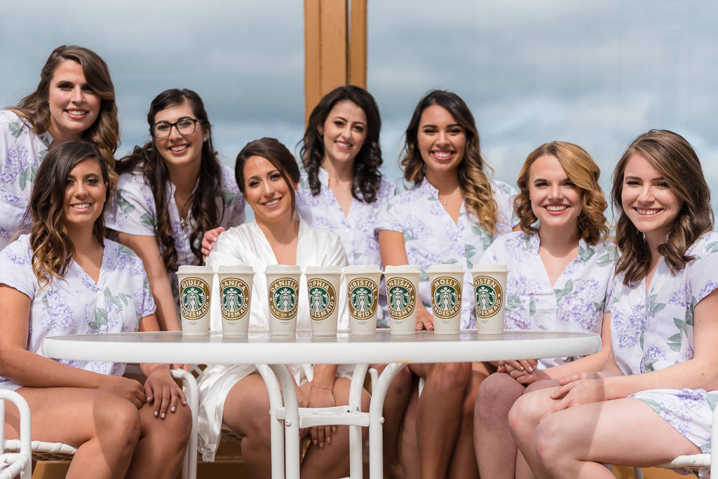 Photo of bridesmaids and brides with personalized Starbucks tumblers.