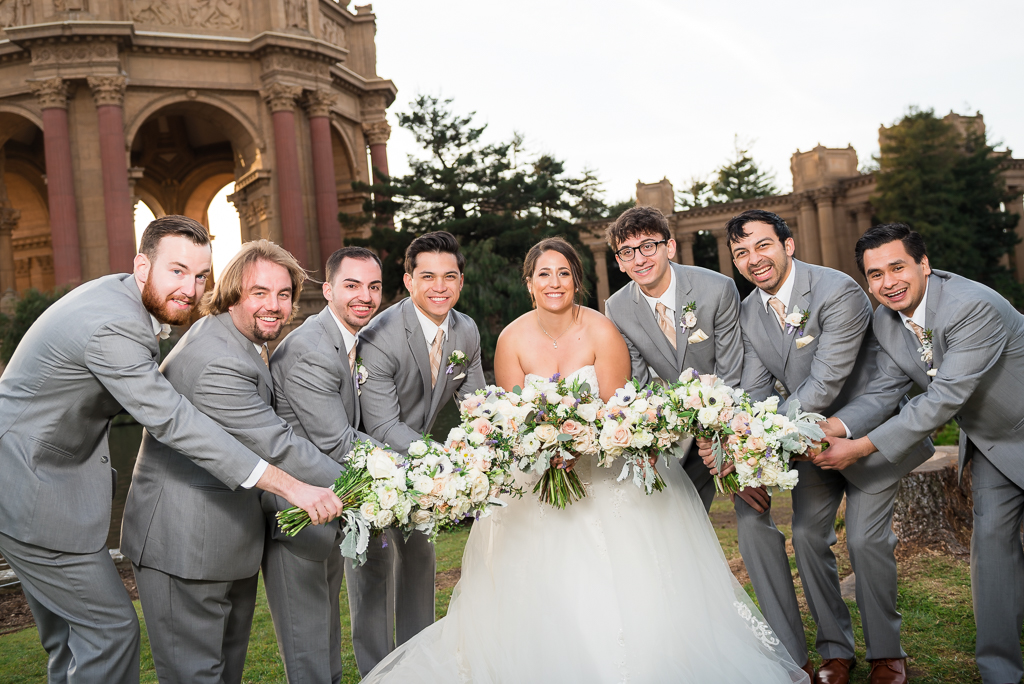 Groomsmen and a bride holding bouquets in a cluster in front of them.