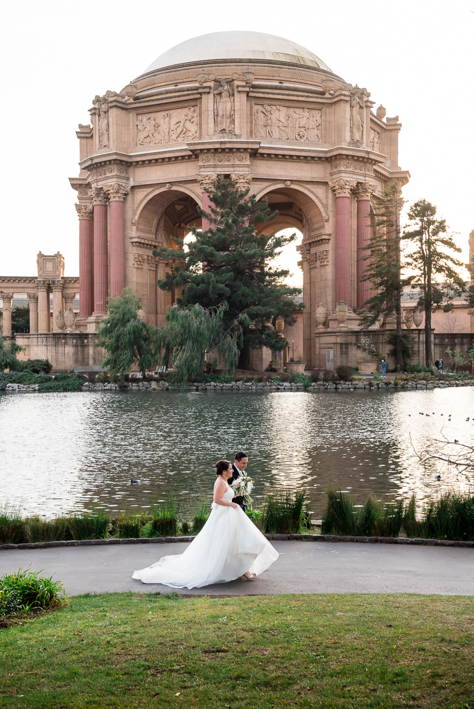 Candid photo of a bride and groom walking along a pond at the Palace of Fine Arts.