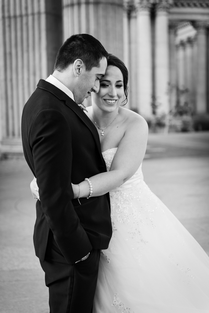 Black and white photo of a brunette bride embracing her new husband.