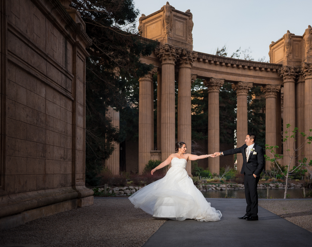 A bride and groom dance with each other alone at a colonnade.