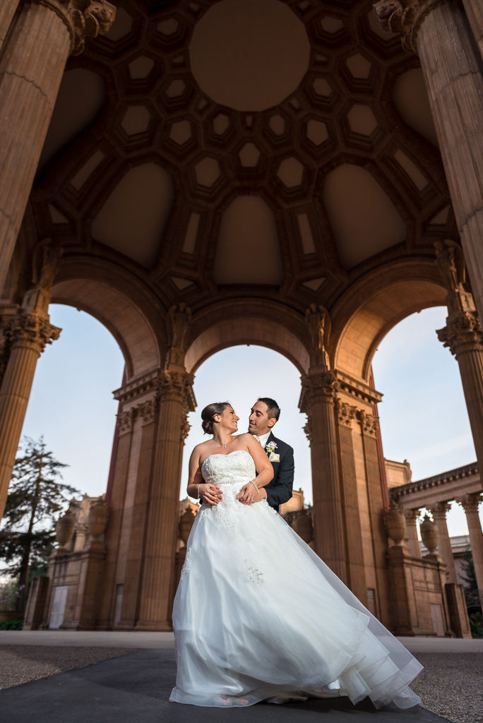 Photo of a bride and groom posing underneath the dome at the Palace of Fine Arts.
