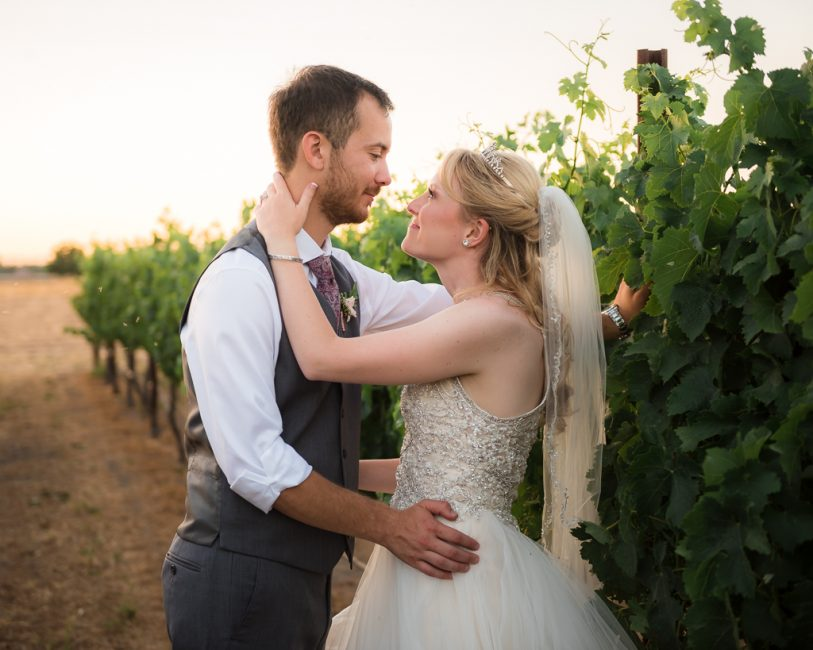 A bride makes eyes at her groom while standing against a vineyard row.