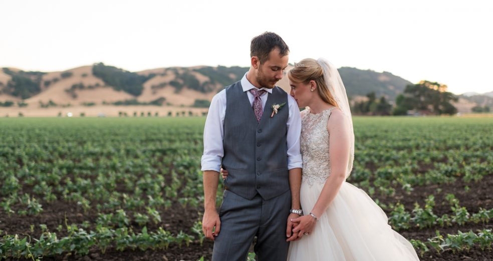 Newlywed bride and groom stand close to eachother in farmland at sunset.
