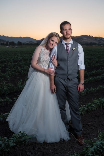 A bride leans against her groom at sunset while standing in a Northern California field.