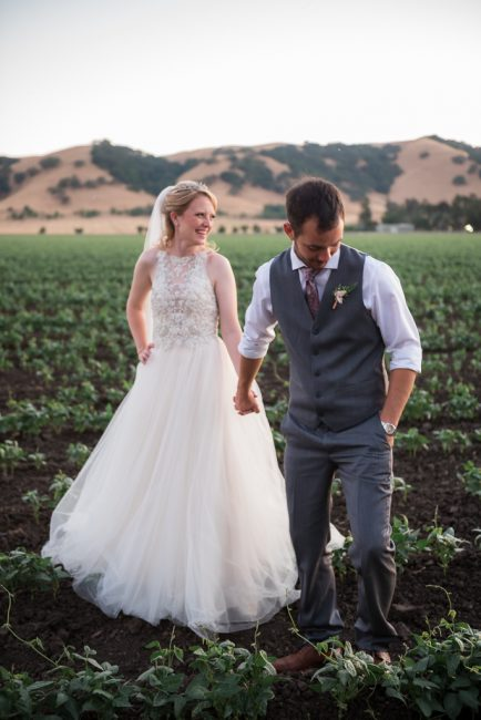 A groom leads his bride across the cultivated rows of farmland at sunset.