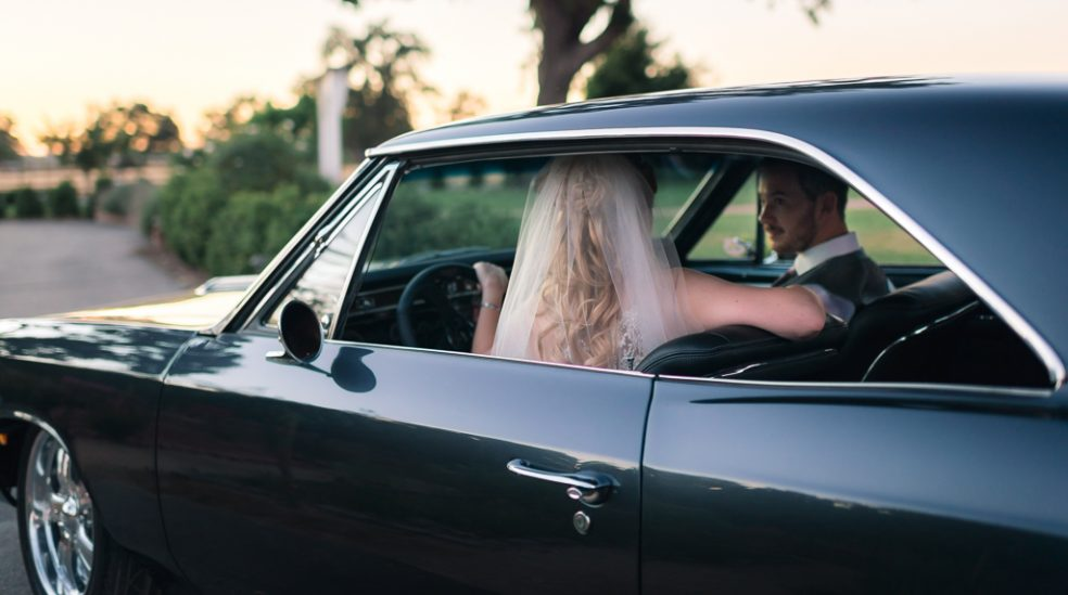 A bride takes the wheel of a classic Chevy muscle car as her husband rides along.