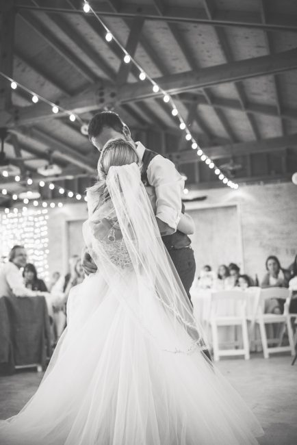 A groom dips his bride during their first dance at their wedding reception.