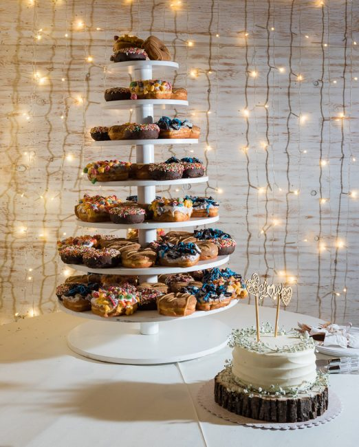 Photo of a wedding cake alongside a doughnut cake at a wedding.