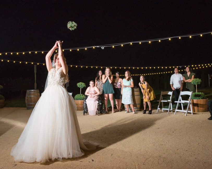 A bride tosses her bouquet to the women standing behind her.