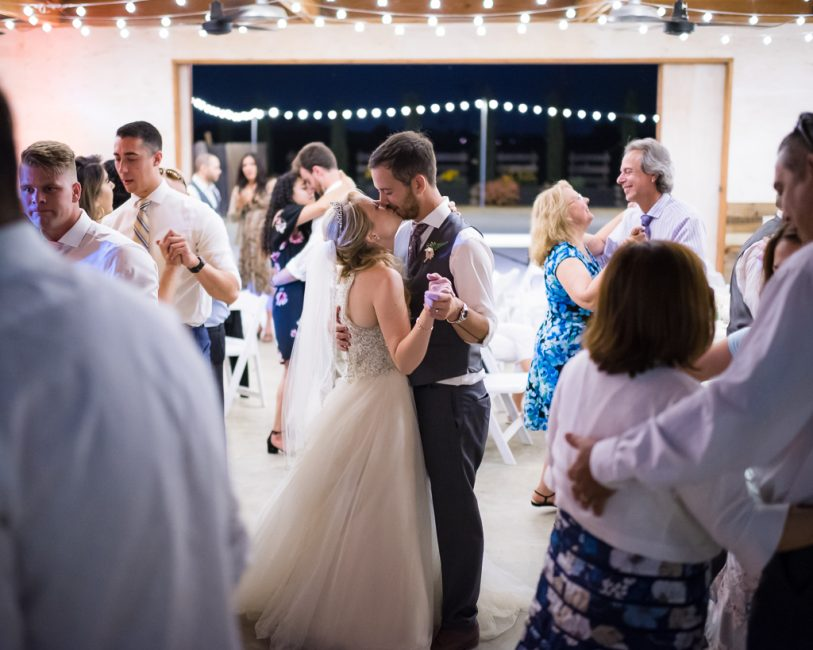 A bride and groom dance closely during their wedding reception.