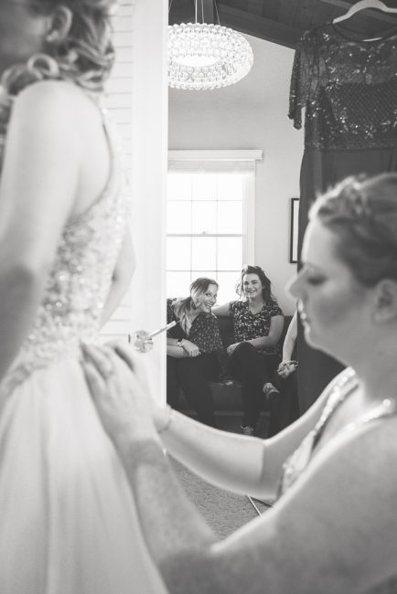 Friends watch as a bride gets help putting on her wedding dress.