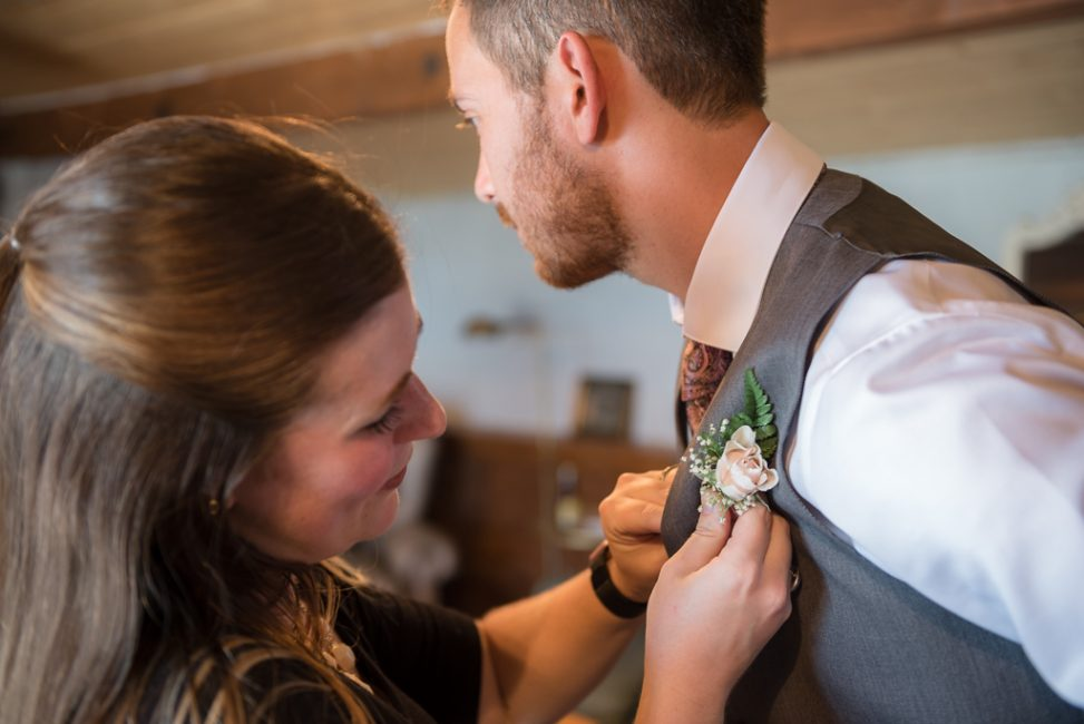 Photograph of a woman placing an orange-colored boutonniere on a bearded man's chest.