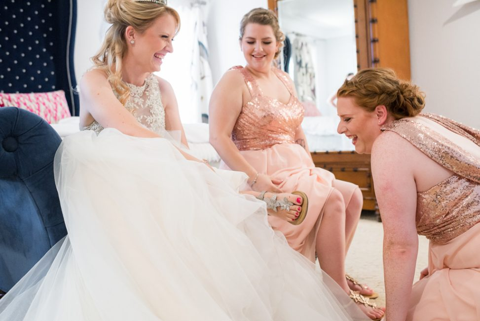 A bride and her bridesmaids joke before the wedding ceremony