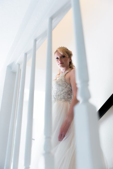 A bride turns while descending a staircase toward her wedding.