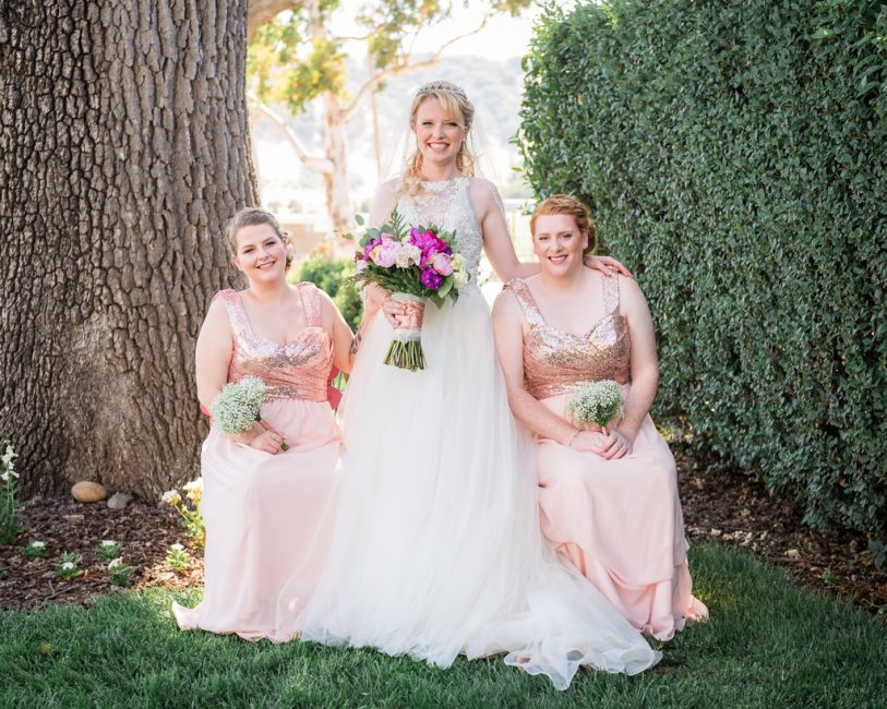 Close up portrait of a bride and her bridesmaids wearing blush dresses.